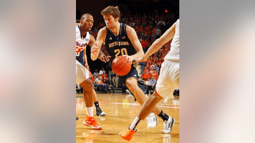 Notre Dame forward Austin Burgett (20) drives past Virginia forward Akil Mitchell during an NCAA college basketball game Saturday, Feb. 22, 2014, in Charlottesville, Va. (AP Photo/Andrew Shurtleff)