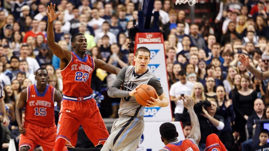 Villanova's Ryan Arcidiacono, second from right, looks to pass the ball while splitting between St. John's Rysheed Jordan, left, and Jakarr Sampson, right, during the second half of an NCAA college basketball game, Saturday, Feb. 22, 2014, in Philadelphia. Villanova won 57-54. (AP Photo/Chris Szagola)