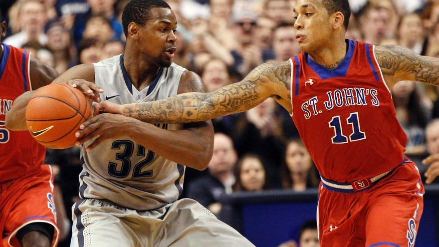 St. John's D'Angelo Harrison, right, reaches in for the ball against Villanova's James Bell, left, during the second half of an NCAA college basketball game, Saturday, Feb. 22, 2014, in Philadelphia. Villanova won 57-54. (AP Photo/Chris Szagola)