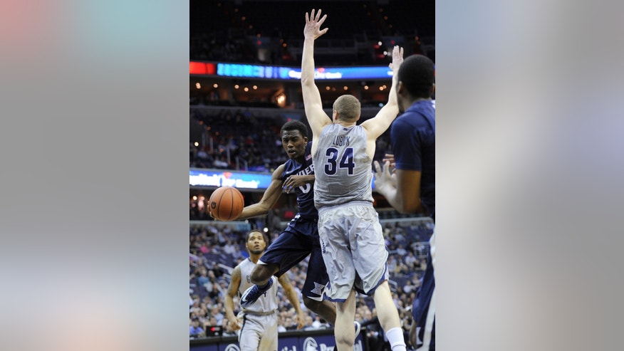 Xavier guard Semaj Christon, left, tries to get around Georgetown forward Nate Lubick (34) to pass the ball during the first half of an NCAA college basketball game, Saturday, Feb. 22, 2014, in Washington. (AP Photo/Nick Wass)
