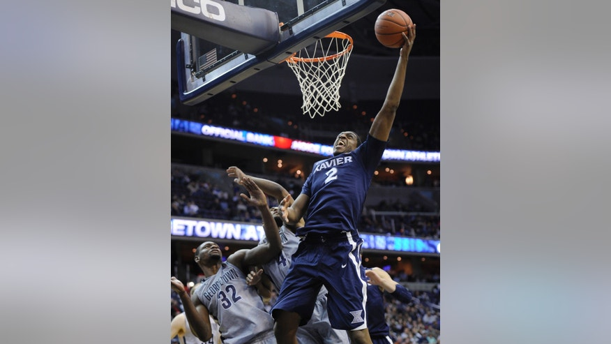 Xavier forward James Farr (2) goes to the basket against Georgetown center Moses Ayegba (32) and D'Vauntes Smith-Rivera (4) during the first half of an NCAA college basketball game, Saturday, Feb. 22, 2014, in Washington. (AP Photo/Nick Wass)