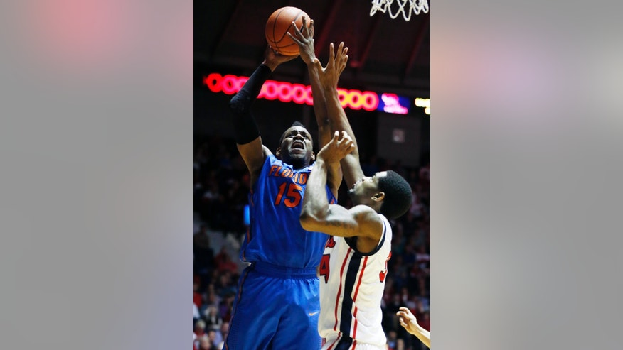 Florida forward Will Yeguete (15) attempts a shot while Mississippi forward Aaron Jones defends in the first half of an NCAA college basketball game in Oxford, Miss., Saturday, Feb. 22, 2014. (AP Photo/Rogelio V. Solis)