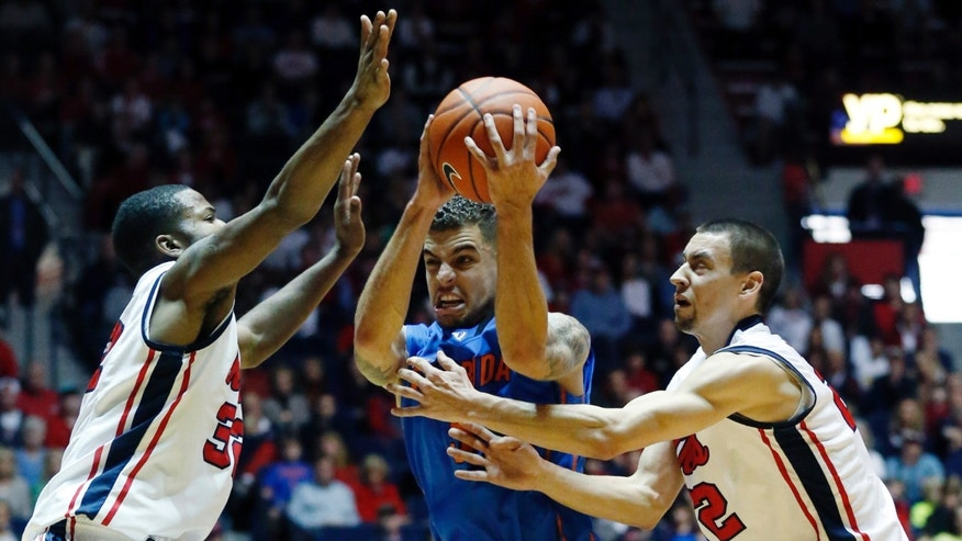 Florida guard Scottie Wilbekin (5) is closely defended by Mississippi guard Jarvis Summers, left, and Marshall Henderson in the first half of an NCAA college basketball game in Oxford, Miss., Saturday, Feb. 22, 2014. (AP Photo/Rogelio V. Solis)