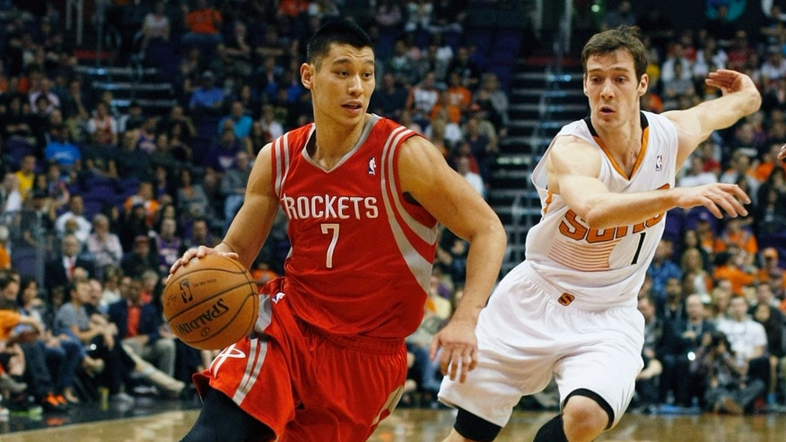 Houston Rockets guard Jeremy Lin (7) drives past Phoenix Suns guard Goran Dragic (1) in the second quarter of an NBA basketball game, Sunday, Feb. 23, 2014, in Phoenix. (AP Photo/Rick Scuteri)