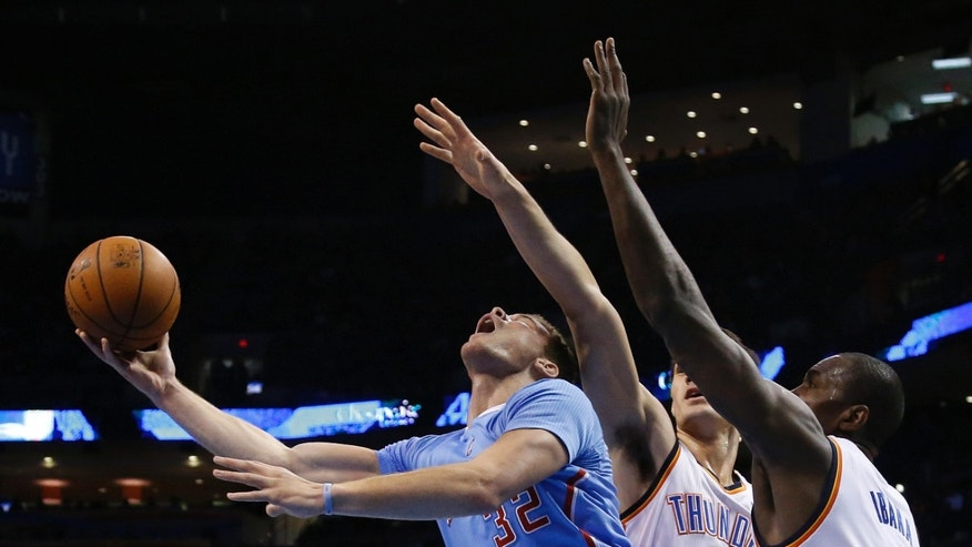 Los Angeles Clippers forward Blake Griffin (32) drives between Oklahoma City Thunder center Steven Adams (12) and forward Serge Ibaka (9) in the first quarter of an NBA basketball game, Sunday, Feb. 23, 2014, in Oklahoma City. (AP Photo/Sue Ogrocki)