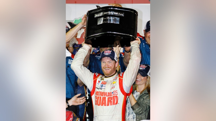 Dale Earnhardt Jr. raises the trophy in Victory Lane after winning the NASCAR Daytona 500 Sprint Cup series auto race at Daytona International Speedway in Daytona Beach, Fla., Sunday, Feb. 23, 2014. (AP Photo/Terry Renna)
