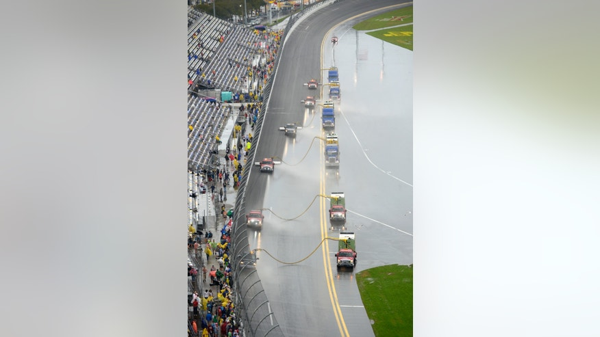 Track personnel attempt to dry the track during the NASCAR Daytona 500 auto race at Daytona International Speedway in Daytona Beach, Fla., Sunday, Feb. 23, 2014. (AP Photo/Phelan M. Ebenhack)