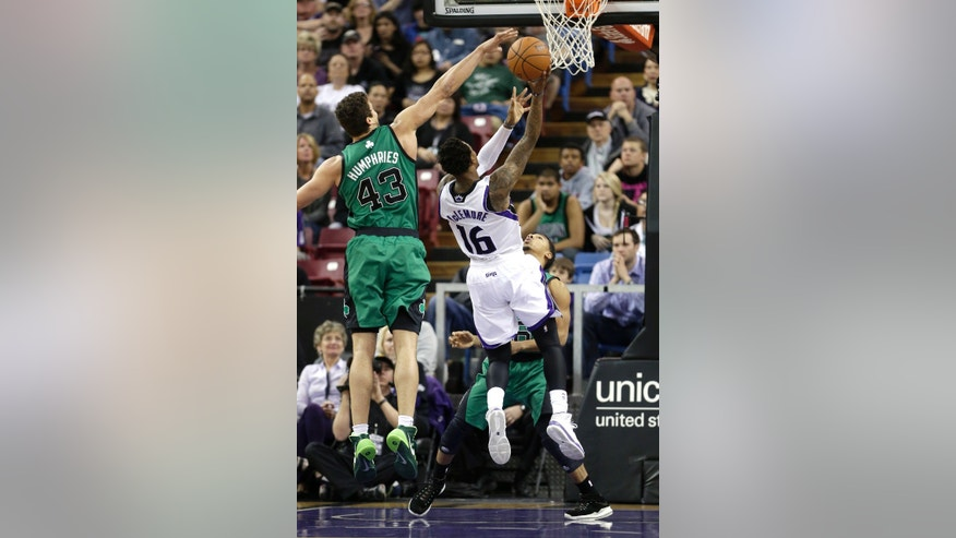 Sacramento Kings guard Ben McLemore, center, drives to the basket against Boston Celtics' Kris Humphries, left, and Phil Pressey, right, during the first quarter of an NBA basketball game in Sacramento, Calif., Saturday, Feb. 22, 2014. (AP Photo/Rich Pedroncelli)