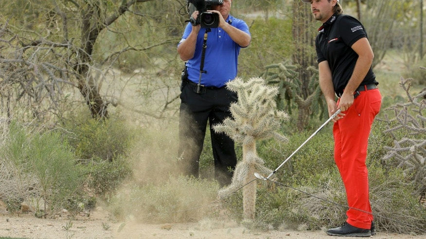 Victor Dubuisson, of France, hits near a cactus on the 19th hole in his championship match against Jason Day, of  Australia, during the Match Play Championship golf tournament, Sunday, Feb. 23, 2014, in Marana, Ariz. (AP Photo/Ted S. Warren)
