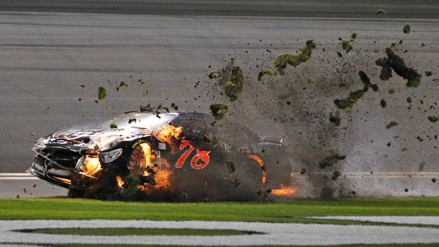 Martin Truex Jr. (78) drives his burning car across the grass after a crash during the second of two NASCAR Sprint Cup series qualifying auto races at Daytona International Speedway in Daytona Beach, Fla., Thursday, Feb. 20, 2014. (AP Photo/Terry Renna)