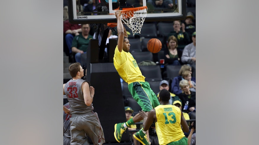 Oregon's Mike Moser, center, dunks the ball past Washington State's Brett Boese, left, and Richard Amardi, right, during the second half of an NCAA college basketball game in Eugene, Ore., Sunday, Feb. 23, 2014. (AP Photo/Chris Pietsch)