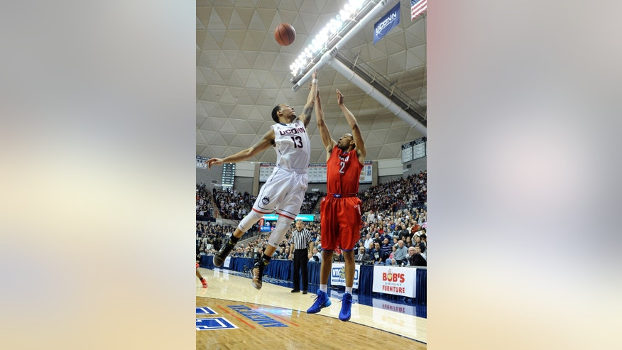 Connecticut's Shabazz Napier (13) guards SMU's Shawn Williams (2) during the first half of an NCAA college basketball game in Storrs, Conn., Sunday, Feb. 23, 2014. (AP Photo/Fred Beckham)