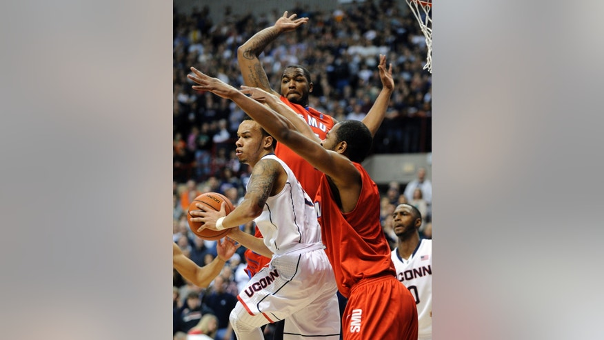Connecticut's Shabazz Napier (13) is guarded by SMU's Markus Kennedy, rear, and Shawn Williams, right, during the first half of an NCAA college basketball game, Sunday, Feb. 23, 2014, in Storrs, Conn. (AP Photo/Fred Beckham)