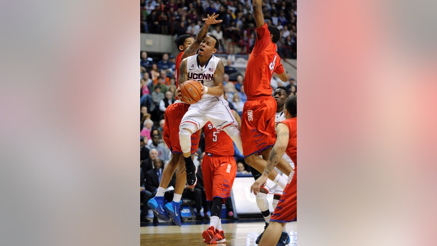 Connecticut's Shabazz Napier (13) is guarded by SMU's Keith Frazier, left, and Ben Moore (34) during the second half of SMU's 64-55 victory in an NCAA college basketball game in Storrs, Conn., Sunday, Feb. 23, 2014. (AP Photo/Fred Beckham)