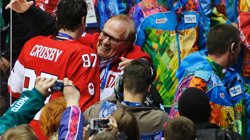 Sidney Crosby of Canada (87) is hugged as he leave the ice after Team Canada won the gold medal in the men's gold medal ice hockey game at the 2014 Winter Olympics, Sunday, Feb. 23, 2014, in Sochi, Russia. (AP Photo/Petr David Josek)