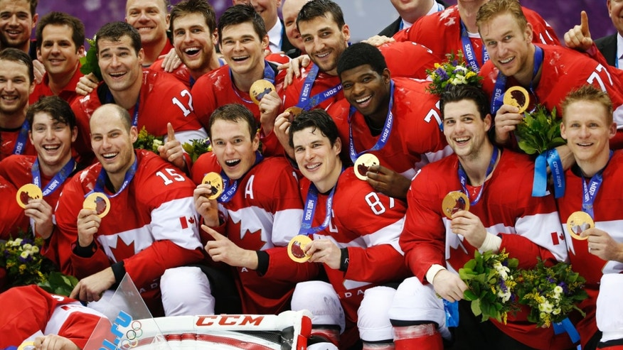 Members of Team Canada pose for a photo with their gold medals after the gold medal men's ice hockey game at the 2014 Winter Olympics, Sunday, Feb. 23, 2014, in Sochi, Russia. Canada defeated Sweden 3-0 in the game. (AP Photo/Mark Humphrey)