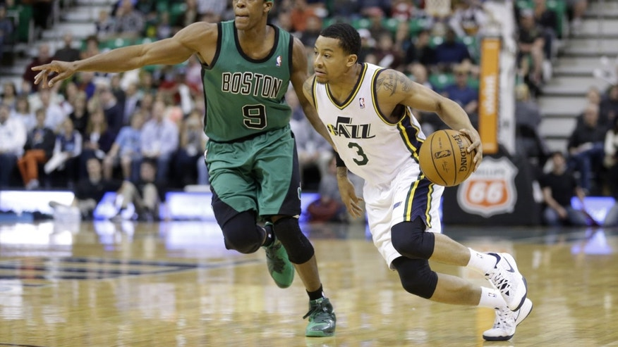 Utah Jazz's Trey Burke (3) drives to the basket as Boston Celtics' Rajon Rondo (9) defends in the first quarter of an NBA basketball game, Monday, Feb. 24, 2014, in Salt Lake City. (AP Photo/Rick Bowmer)