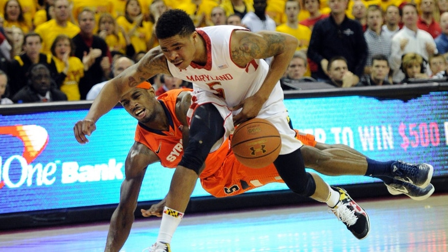 Syracuse forward C.J. Fair, left, fights for the ball against Maryland guard Nick Faust (5) during the second half of an NCAA college basketball game, Monday, Feb. 24, 2014, in College Park, Md. Fair was called for a foul on the play. Syracuse won 57-55. (AP Photo/Nick Wass)