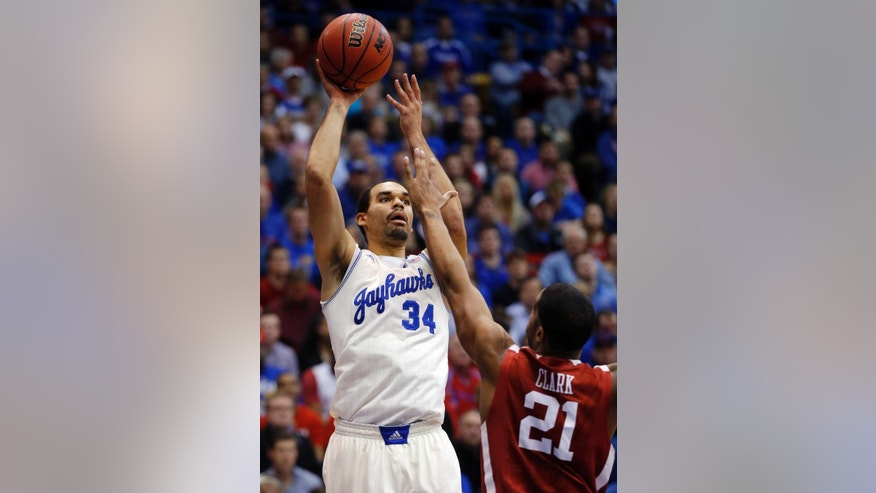 Kansas forward Perry Ellis (34) shoots over Oklahoma forward Cameron Clark (21) during the first half of an NCAA college basketball game in Lawrence, Kan., Monday, Feb. 24, 2014. (AP Photo/Orlin Wagner)