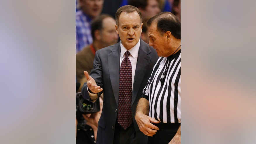 Oklahoma head coach Lon Kruger talks with a referee during the first half of an NCAA college basketball game against Kansas in Lawrence, Kan., Monday, Feb. 24, 2014. (AP Photo/Orlin Wagner)