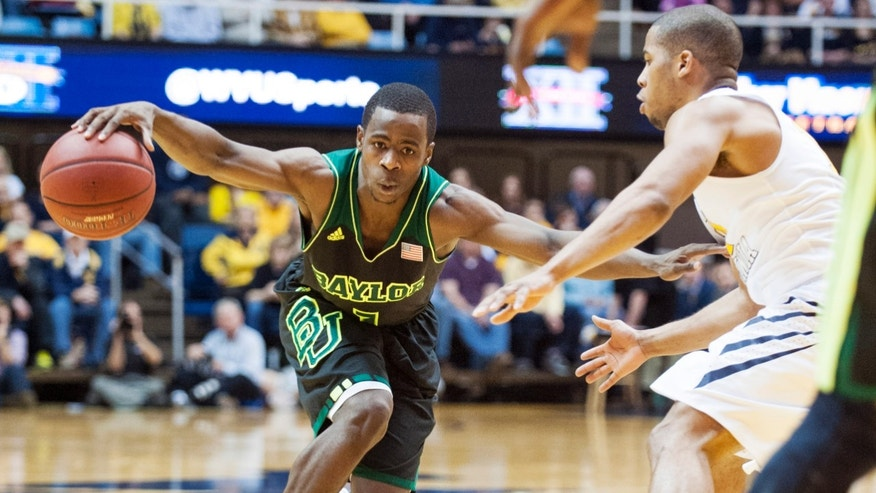 Baylor's Kenny Chery, left, drives by West Virginia's Gary Browne during the second half of an NCAA college basketball game Saturday, Feb. 22, 2014, in Morgantown, W.Va. Baylor won 88-75. (AP Photo/Andrew Ferguson)