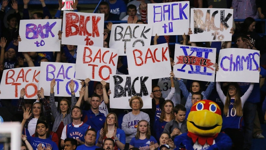 Kansas fans celebrate gaining a share of their tenth straight Big-12 championship during the second half of an NCAA college basketball game against Oklahoma in Lawrence, Kan., Monday, Feb. 24, 2014. Kansas defeated Oklahoma 83-75. (AP Photo/Orlin Wagner)