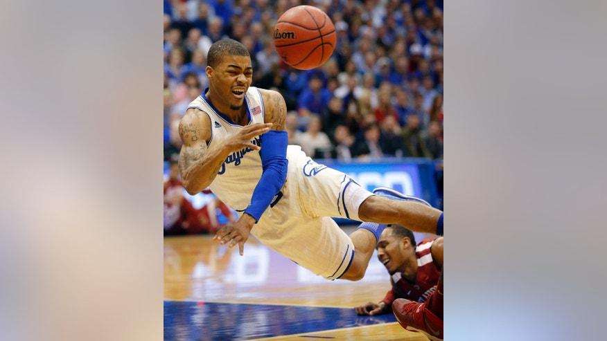 Kansas guard Frank Mason (0) passes the ball after being fouled by Oklahoma guard Jordan Woodard, right, during the first half of an NCAA college basketball game in Lawrence, Kan., Monday, Feb. 24, 2014. (AP Photo/Orlin Wagner)
