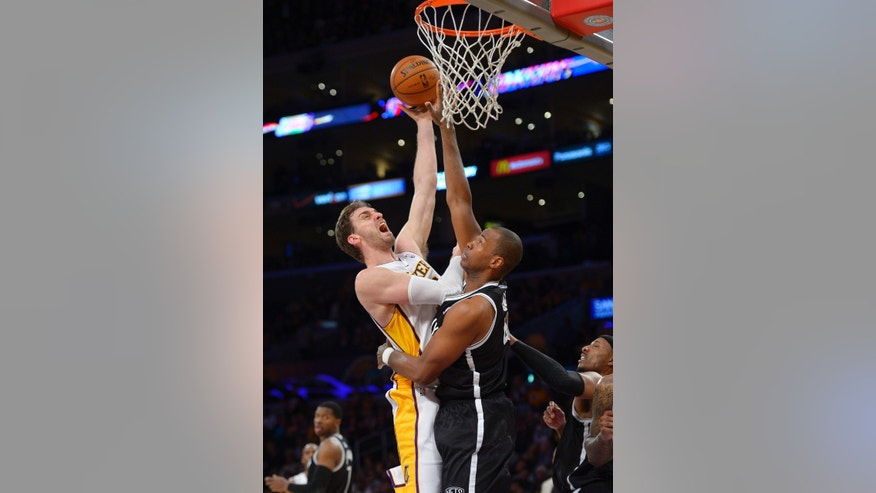 Los Angeles Lakers center Pau Gasol, left, of Spain, puts up a shot as Brooklyn Nets center Jason Collins defends during the second half of an NBA basketball game, Sunday, Feb. 23, 2014, in Los Angeles. The Nets won 108-102. (AP Photo/Mark J. Terrill)