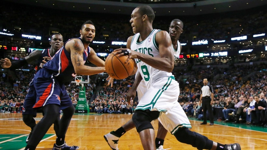 Boston Celtics guard Rajon Rondo (9) drives against Atlanta Hawks forward Mike Scott and guard Dennis Schroder, left rear, during the first quarter of an NBA basketball game in Boston, Wednesday, Feb. 26, 2014. (AP Photo/Elise Amendola)