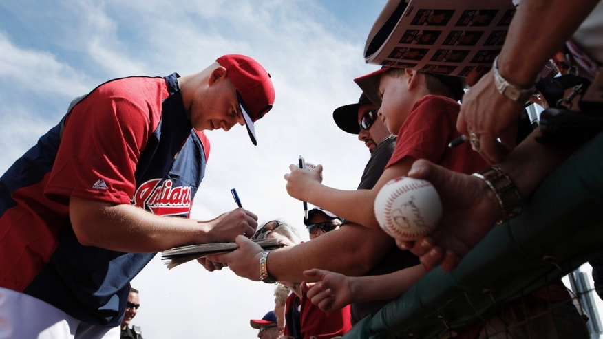 Cleveland Indians pitcher Justin Masterson signs autographs before an exhibition baseball game against the Cincinnati Reds in Goodyear, Ariz., Wednesday, Feb. 26, 2014. (AP Photo/Paul Sancya)