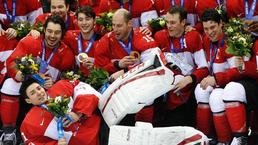 Canada goalie Carey Price, front, lies on the ice as he poses with teammates after Canada beat Sweden 3-0 in the men's ice hockey gold medal game at the 2014 Winter Olympics, Sunday, Feb. 23, 2014, in Sochi, Russia. (AP Photo/Mark Humphrey)