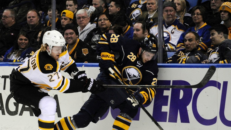 Boston Bruins'  Dougie Hamilton (27) checks Buffalo Sabres' Zemgus Girgensons (28) during the first period of an NHL hockey game in Buffalo, N.Y., Wednesday, Feb. 26, 2014. (AP Photo/Gary Wiepert)