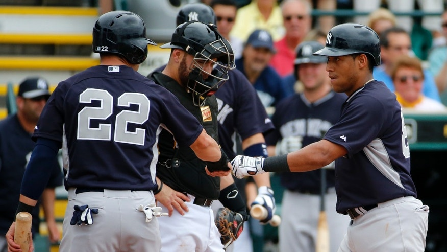New York Yankees' Ramon Flores, right, scores past Pittsburgh Pirates catcher Russell Martin, center, and is greeted by Jacoby Ellsbury (22), who was on base for his two-run home run off Pittsburgh Pirates pitcher Edinson Volquez in the second inning of a spring training baseball game in Bradenton, Fla.,  Wednesday, Feb. 26, 2014. The Pirates won 6-5. (AP Photo/Gene J. Puskar)