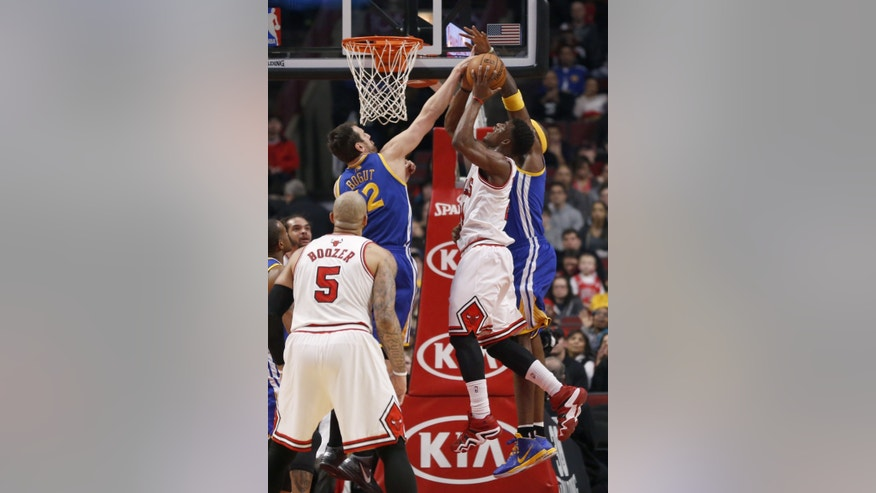 Chicago Bulls shooting guard Jimmy Butler (21) is fouled by Golden State Warriors center Jermaine O'Neal, right, as Andrew Bogut (12) also defends during the first half of an NBA basketball game, Wednesday, Feb. 26, 2014, in Chicago. Watching the play is Carlos Boozer (5). (AP Photo/Charles Rex Arbogast)