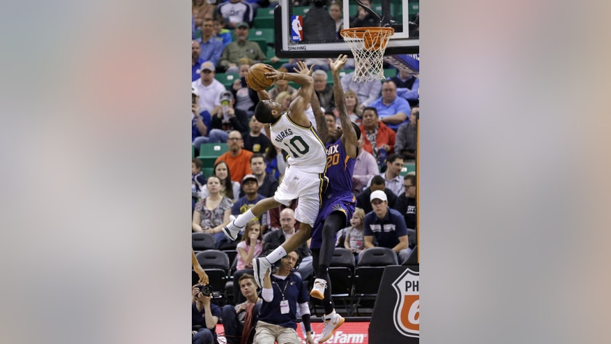 Utah Jazz's Alec Burks (10) shoots as he is fouled by Phoenix Suns' Archie Goodwin (20) in the second quarter of an NBA basketball game on Wednesday, Feb. 26, 2014, in Salt Lake City. (AP Photo/Rick Bowmer)