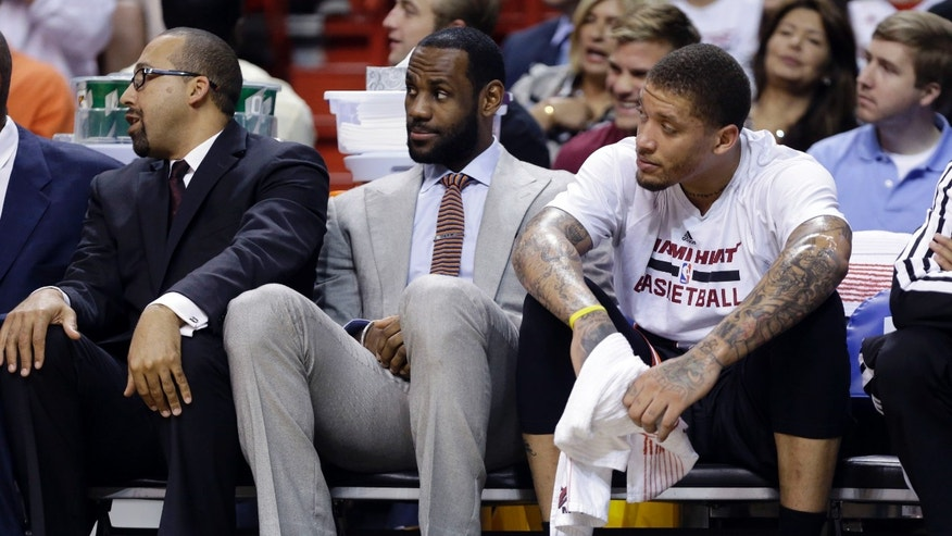 Miami Heat's LeBron James, center, watches from the bench with teammate Michael Beasley, right, during the first half of an NBA basketball gam against the Chicago Bulls, Sunday, Feb. 23, 2014, in Miami. James is not playing as he is recovering from a broken nose. (AP Photo/Lynne Sladky)