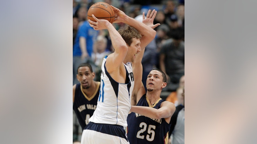 Dallas Mavericks' forward Dirk Nowitzki (41) looks to pass as New Orleans Pelicans' Austin Rivers (25) defends during the first half of an NBA basketball game on Wednesday, Feb. 26, 2014, in Dallas. (AP Photo/Brandon Wade)