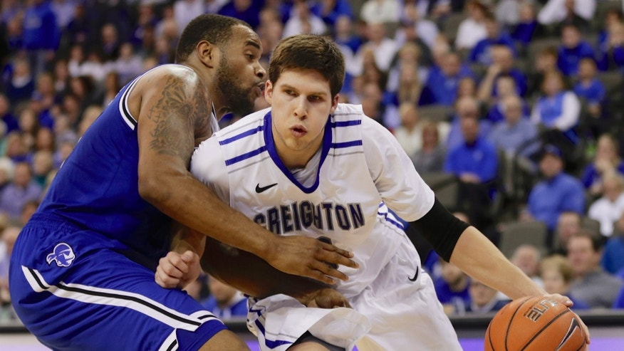 Creighton's Doug McDermott, right, drives around Seton Hall's Eugene Teague, left, in the second half of an NCAA college basketball game in Omaha, Neb., Sunday, Feb. 23, 2014. Creighton won 72-71. (AP Photo/Nati Harnik)