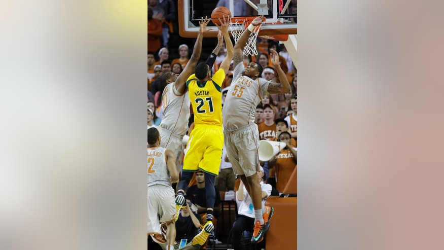 Texas' Jonathan Holmes (10) and Cameron Ridley (55) defend Baylor's Isaiah Austin (21) as he tries to score during the first half of an NCAA college basketball game, Wednesday, Feb. 26, 2014, in Austin, Texas. (AP Photo/Eric Gay)