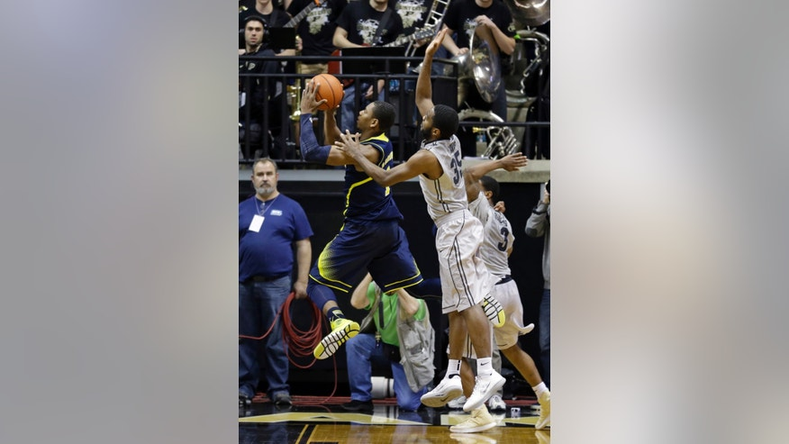 Michigan forward Glenn Robinson III, left, hits a bucket in front of Purdue guard Rapheal Davis as time expires in overtime to give Michigan a 77-76 win an NCAA college basketball game in West Lafayette, Ind., Wednesday, Feb. 26, 2014.  (AP Photo/Michael Conroy)