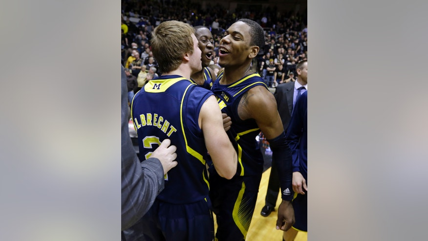 Michigan forward Glenn Robinson III, right, is hugged by teammates Spike Albrecht, left, and Caris LeVert after hitting a game-winning shot as time expired in overtime against Purdue in an NCAA college basketball game in West Lafayette, Ind., Wednesday, Feb. 26, 2014. Michigan defeated Purdue 77-76. (AP Photo/Michael Conroy)