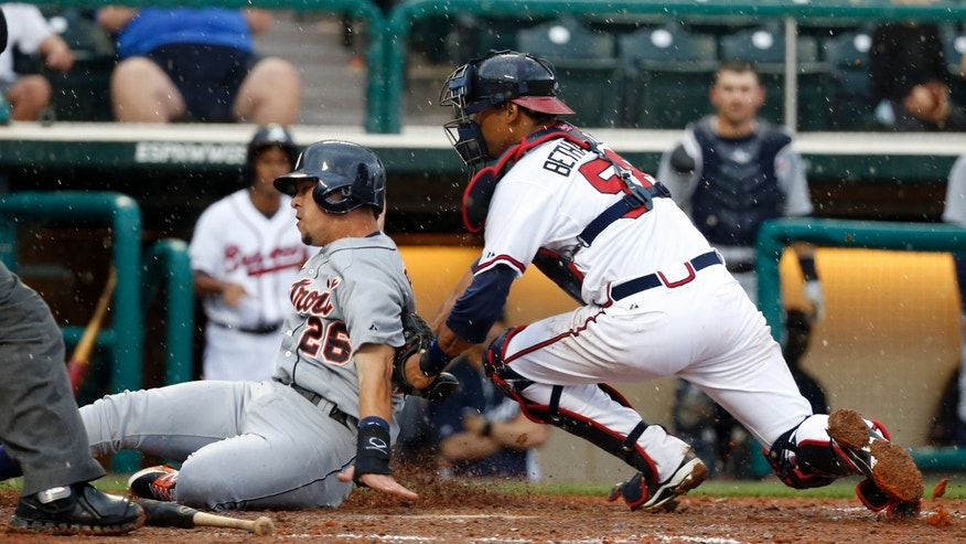 Atlanta Braves catcher Christian Bethancourt tags Detroit Tigers' Hernan Perez for the out at home in the ninth inning of a spring training baseball game, Wednesday, Feb. 26, 2014, in Kissimmee, Fla. The Tigers won 6-5. The game was stopped because of rain with two outs in the bottom of the ninth, and the Tigers were awarded the win. (AP Photo/Alex Brandon)