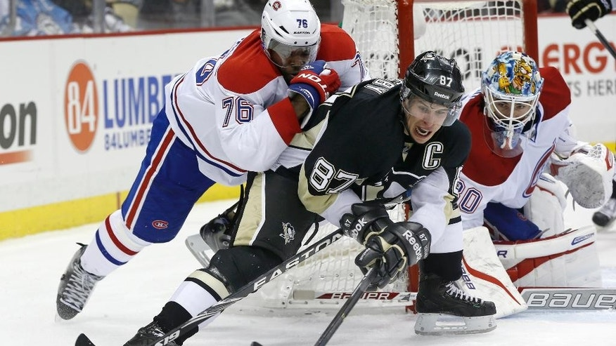Pittsburgh Penguins' Sidney Crosby (87) brings the puck from behind the goal as P.K. Subban (76) defends and goalie Peter Budaj, of Slovakia, keeps watch during the second period of an NHL hockey game, Thursday, Feb. 27, 2014 in Pittsburgh. (AP Photo/Keith Srakocic)