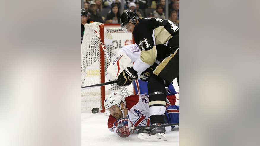 The puck bounces in front of Montreal Canadiens' Josh Gorges (26) as Pittsburgh Penguins' Evgeni Malkin (71), of Russia tries to control it during the second period of an NHL hockey game, Thursday, Feb. 27, 2014 in Pittsburgh. (AP Photo/Keith Srakocic)