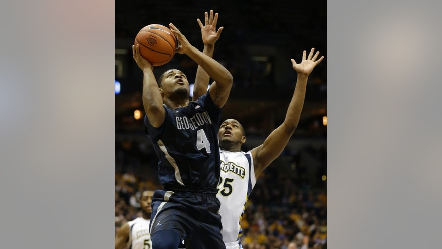 Georgetown's D'Vauntes Smith-Rivera (4) drives against Marquette's Steve Taylor Jr., right, during the second half of an NCAA college basketball game on Thursday, Feb. 27, 2014, in Milwaukee. (AP Photo/Jeffrey Phelps)