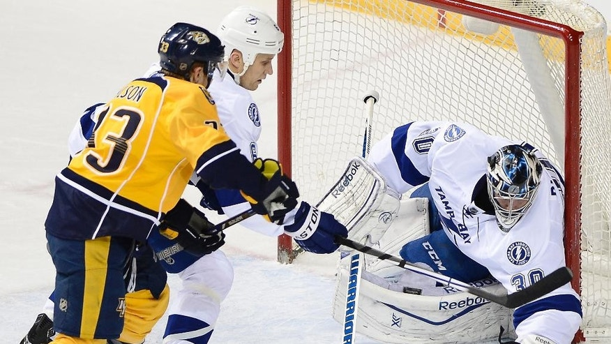 Tampa Bay Lightning goalie Ben Bishop (30) gloves a shot by Nashville Predators forward Colin Wilson (33) as Lightning defenseman Sami Salo, center, of Finland, defends in the first period of an NHL hockey game, Thursday, Feb. 27, 2014, in Nashville, Tenn. (AP Photo/Mark Zaleski)