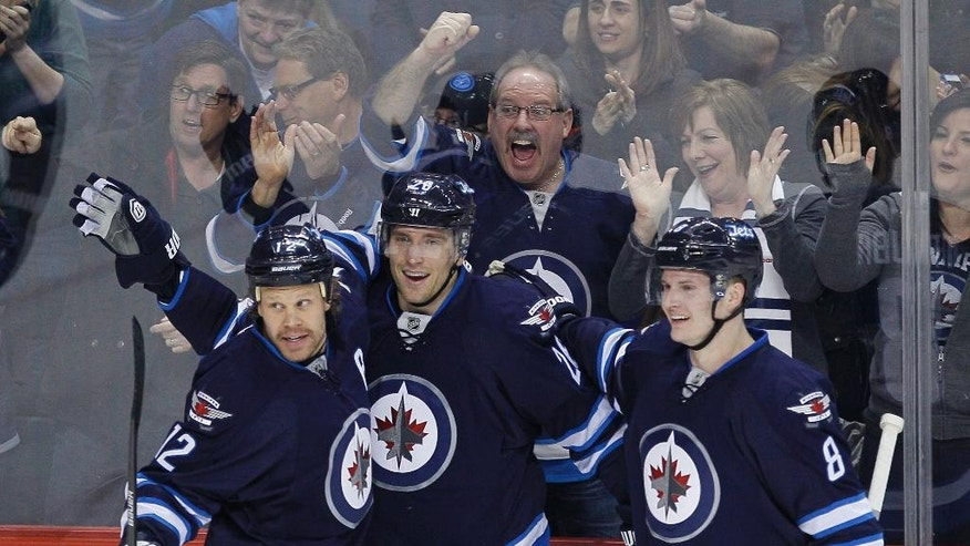 Winnipeg Jets' Olli Jokinen (12), Blake Wheeler (26) and Jacob Trouba (8) celebrate Wheeler's goal against the Phoenix Coyotes during first-period NHL hockey game action in Winnipeg, Manitoba, Thursday, Feb. 27, 2014. (AP Photo/The Canadian Press, John Woods)