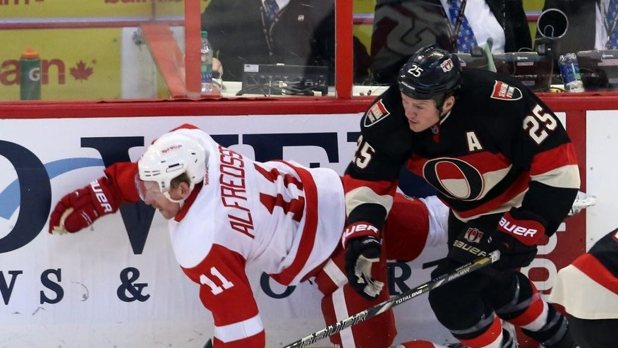 Ottawa Senators' Chris Neil (25) checks Detroit Red Wings' Daniel Alfredsson (11) during second period NHL hockey action in Ottawa, Thursday, Feb. 27, 2014. (AP Photo/The Canadian Press, Fred Chartrand)