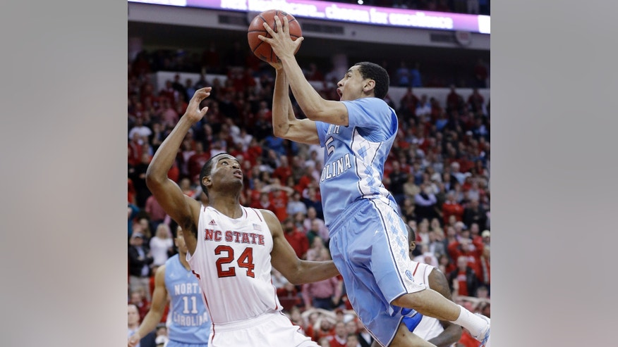North Carolina's Marcus Paige (5) drives to the basket for the game-winning shot in overtime against North Carolina State's T.J. Warren (24) in an NCAA college basketball game in Raleigh, N.C., Wednesday, Feb. 26, 2014. North Carolina won 85-84. (AP Photo/Gerry Broome)