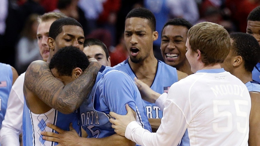 North Carolina's Leslie McDonald, left, hugs Marcus Paige as teammates celebrate Paige's shot in overtime following an NCAA college basketball game in Raleigh, N.C., Wednesday, Feb. 26, 2014. North Carolina defeated North Carolina State 85-84 in overtime. (AP Photo/Gerry Broome)